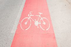 Bike lane painted in red as caution on the asphalt road with bicycle sign or symbol.  Royalty Free Stock Image