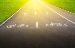 Bike Lane, symbol on the road for bicycles with yellow light beam. Close up bike Lane, symbol on the road for bicycles with yellow light beam Royalty Free Stock Images