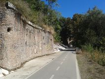 Bike lane to Rome with an ancient wall of stone with some graffiti and vegetation around, Italy. Blue clear sky. Sunny day. Hot day. Trees and tall grass stock images