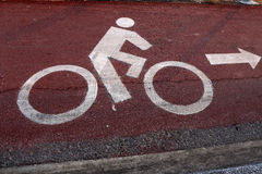 Bike lanes. And white bike symbol on brown road stock photography