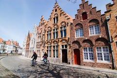 Bike le case di Bruges del passaggio, l'ombra dell'albero sfrondato Immagini Stock Libere da Diritti