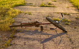 The bike lies on the road at sunset Royalty Free Stock Image