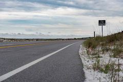 Bike Line Sign In Pensacola. Empty Road and Cloudy Sky.  Stock Photos