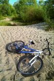 Bike lying on the sand. The sand is hard to ride a cyclist. Nobody, trees in the background. Left the bike. Woman`s bike lying on the sand. The sand is hard to royalty free stock photography