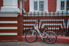 The bike near the red house. The bike is on the street at the red house Royalty Free Stock Photo