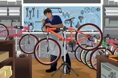 Bike o reparador que repara uma bicicleta em sua loja Imagens de Stock Royalty Free