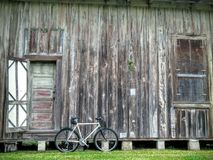 Bike and Old Weathered Barn. White bicycle with old weathered barn background Royalty Free Stock Photos