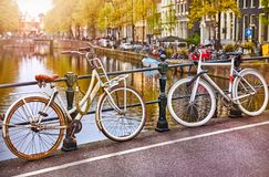 Bike over canal Amsterdam city. Picturesque town landscape in Netherlands with view on river Amstel. Stock Photos
