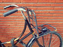Bike with parcel carrier. Closeup of ladies bicycle with covered security chain and front parcel carrier, background of red brick wall Stock Image