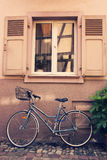 Bike parked under a window Royalty Free Stock Photography