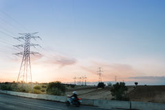 Bike passando una strada contro le torri ad alta tensione al tramonto Fotografia Stock