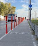 Bike path in the park fenced with red road columns Stock Photography