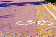 Bike path sign. Path paved with cobblestones, coming in the dist. Bike route sign on the pavement in sunlight in a park. The ecological mode of transport. The Stock Photography