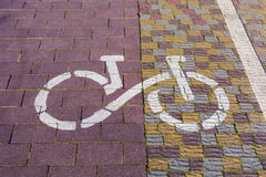 Bike path sign. Path paved with cobblestones, coming in the dist. Bike route sign on the pavement in sunlight in a park. The ecological mode of transport. The Stock Photo