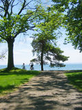 Bike path to lake. Daughter and Father biking down a trail to Lake Ontario on a summer day stock image