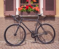 Bike placed under a window full of flowers stock photography