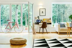 Bike and pouf in room. Red bike and pouf in living room with rolls of paper in basket next to black chair at desk with laptop and lamp Royalty Free Stock Photography