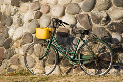 Bike propped on wall. A green bike with yellow basket propped against a stone wall Stock Photography