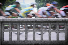 Bike race. Quick ciclysts on a bridge Royalty Free Stock Photography