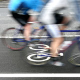 Bike race. In denmark, cyclist are passing by a bike sign on the road. Shot with low shutter speed to achieve motion blur Stock Image