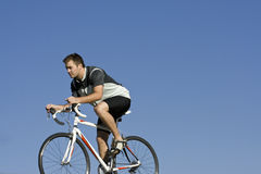 Bike Racer. An attractive young male biker with a determined face rides his road bike. Lots of room for copy Royalty Free Stock Photography