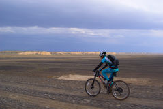 Bike racer in storm desert Stock Photography