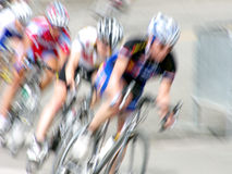Bike Racers. Professional female bicycle racers rounding a turn, intentionally blurred Stock Image