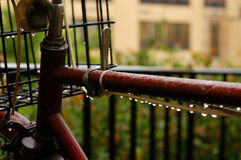 Bike in rain 2. A bike with basket in the rain. Bike is very old and neglected; low key Royalty Free Stock Images