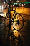 Bike on the rain in New York. Parked bike in wet golden street. New York stock photos