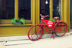Bike rental service. Red viintage bicycle parked on the city street. Urban scene. Vintage photo Royalty Free Stock Photography