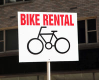 Bike Rental Sign. Bike rental sign with a bike image and red letters on a brick building background stock images