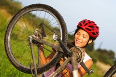 Bike repair. Woman repairing mountain bike. Beautiful smiling woman Stock Image