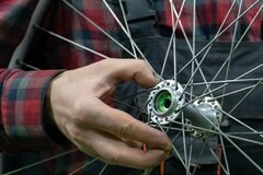 Free Bike Repair. A Mechanic Holds In His Hand The Front Wheel Of A Road Bike. Maintenance Of The Hub, Replacement Of Grease And Royalty Free Stock Photography - 214081737