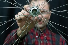 Free Bike Repair. A Mechanic Holds In His Hand The Front Wheel Of A Road Bike. Maintenance Of The Hub, Replacement Of Grease And Royalty Free Stock Photo - 215273305
