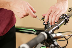 Bike repair. Bicycle fixing. Hex wrench works. Man configures th Royalty Free Stock Images