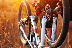 Bike repair. Young man repairing mountain bike Stock Photography
