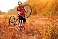 Bike repair. Young man repairing mountain bike Stock Images