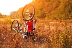 Bike repair. Young man repairing mountain bike Royalty Free Stock Images