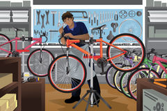 Bike repairman repairing a bicycle in his shop Royalty Free Stock Images
