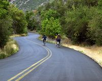 Bike ride. Three friends on bicycles riding down a canyon road Stock Images