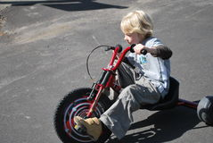 Speedy Child on a Bike. Blond boy speeding on a red low rider three wheeled bike on a concrete driveway Stock Photography