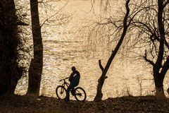 Bike rider on the edge of a river looking at the sunset. Sepia colors Stock Image