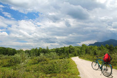 Bike riding at isar wetlands, with dramatic cloudy sky, lonely b Stock Photo