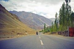 Bike riding by mountain road straight, to mountain Stock Photo
