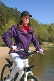 Bike riding - woman on bike in forest near lake Stock Photography