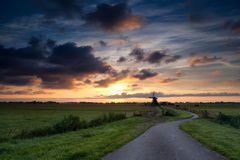 Bike road to windmill at sunrise Royalty Free Stock Photography