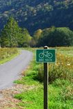 Bike Route Sign. View of sign marking  bike route, with bike trail and countryside in background Stock Photography