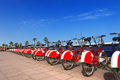 Bike Sharing in Barcelona Spain. Long row of red and white bicycles (public bikes) near the harbor in Ronda Litoral, Barcelona - Spain Stock Images