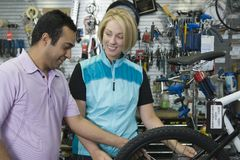 Bike shop assistant helping female cyclist Royalty Free Stock Image