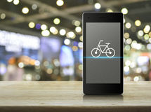Bike shop online concept. Bicycle flat icon on modern smart phone screen on wooden table over blur light and shadow of shopping mall, Bike shop online concept Stock Images